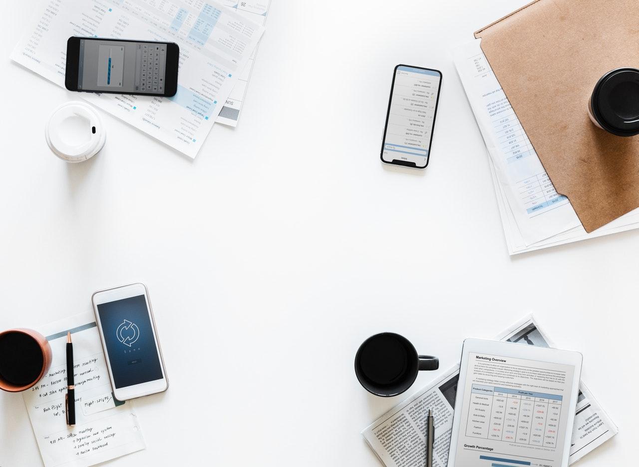 Телефони и чаши с кафе на работна маса